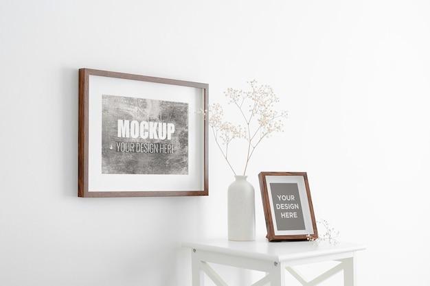 Mockup di cornici di paesaggi e ritratti su muro bianco con pianta di gypsophila secca in vaso