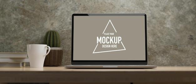 Display per laptop per mockup su tavolo in legno con caffè cactus libri stanza muro di cemento sotto la luce