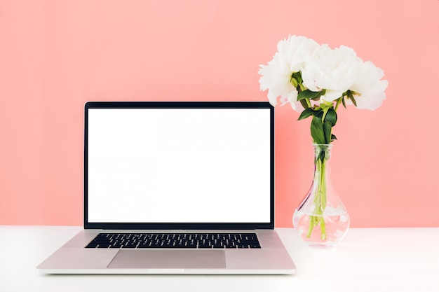 Computer portatile con lo schermo in bianco bianco e fiori in vaso sulla tavola