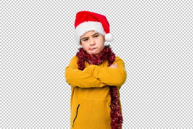 Il ragazzino che celebra il giorno di natale che porta un fronte accigliato isolato cappello di santa nel dispiacere, tiene le armi piegate.