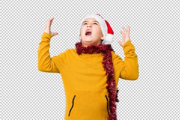Il ragazzino che celebra il giorno di natale che porta un cappello di santa ha isolato le grida al cielo, cercante, frustrato.