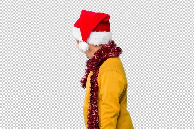 Il ragazzino che celebra il giorno di natale che porta un cappello di santa ha isolato gridare verso uno spazio della copia