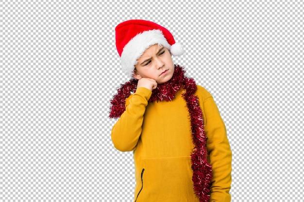 Il ragazzino che celebra il giorno di natale che porta un cappello di santa ha isolato chi si sente triste e pensieroso, esaminando lo spazio della copia.