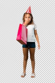 Bambina ad una festa di compleanno che tiene una bocca della copertura del sacchetto del regalo con le mani
