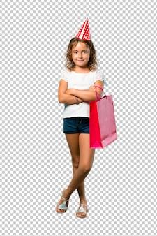 Bambina a una festa di compleanno in possesso di un sacchetto regalo tenendo le braccia incrociate