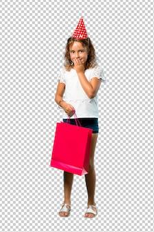 Bambina ad una festa di compleanno che tiene una risata del sacchetto del regalo