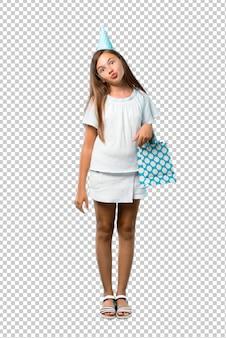 La bambina ad una festa di compleanno che tiene un sacchetto del regalo fa l'emozione facciale divertente e pazza