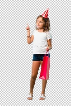 Bambina ad una festa di compleanno che tiene un sacchetto del regalo che indica con il dito indice una grande idea
