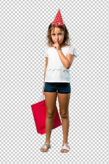 Bambina a una festa di compleanno in possesso di un sacchetto regalo mostrando un segno di chiusura della bocca