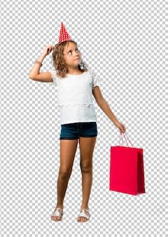 Bambina ad una festa di compleanno che tiene un sacchetto del regalo che sta e che pensa un'idea