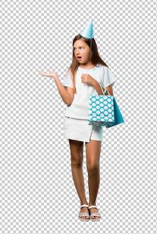 Bambina ad una festa di compleanno che tiene un sacchetto del regalo infelice e frustrato con qualcosa