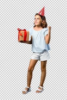 Bambina ad una festa di compleanno che tiene un regalo che celebra una vittoria
