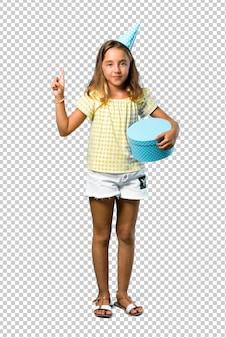 Bambina ad una festa di compleanno che tiene un regalo che conta il segno di numero uno