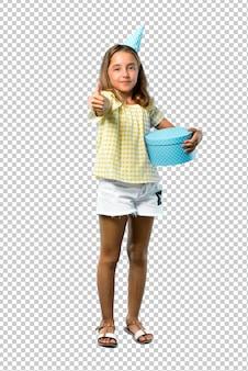 Bambina ad una festa di compleanno che tiene un regalo che dà pollici aumenta il gesto e sorridere