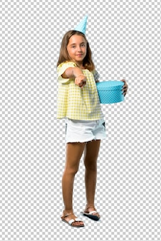 La bambina ad una festa di compleanno che tiene un regalo indica il dito voi