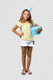 Bambina ad una festa di compleanno che tiene un regalo che posa con le armi all'anca
