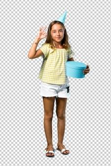 Bambina ad una festa di compleanno che tiene un regalo che mostra un segno giusto con le dita
