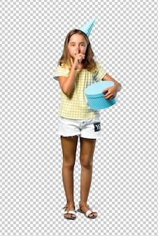 Bambina ad una festa di compleanno in possesso di un regalo che mostra un segno di chiusura bocca e gesto di silenzio