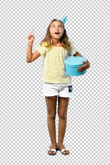Bambina ad una festa di compleanno in possesso di un regalo in piedi e pensando un'idea