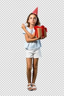 Bambina ad una festa di compleanno che tiene un regalo infelice e frustrato con qualcosa