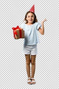 Bambina ad una festa di compleanno che tiene un regalo con sorpresa e scioccato espressione facciale