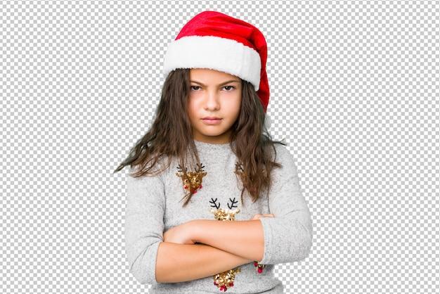 La bambina che celebra il giorno di natale che aggrotta le sopracciglia nel dispiacere, tiene le braccia conserte.