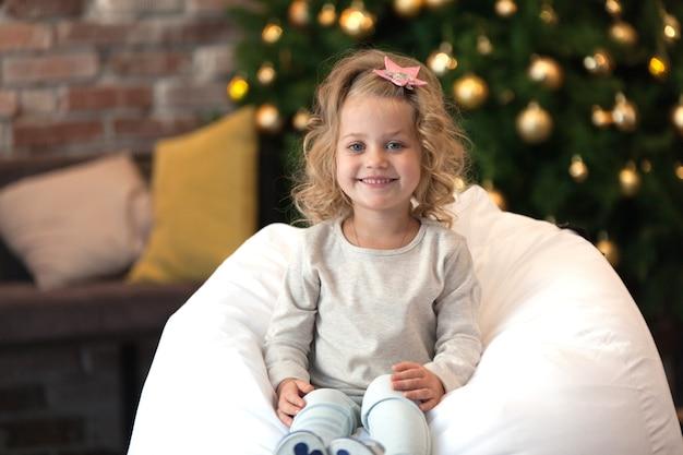 Bambina accanto all'albero di natale, con maglione mockup per il tuo design