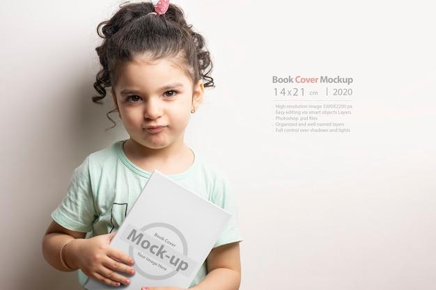 Bambina che tiene un libro per bambini con copertina in bianco nella parte anteriore del corpo