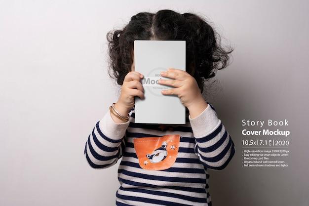 Bambina che tiene un libro di storie per bambini con mockup di copertina Psd Premium