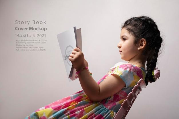 Bambina che legge un libro con copertina vuota davanti al corpo
