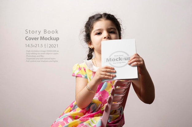 Bambina che legge un romanzo con copertina vuota davanti al corpo, serie di mock-up psd modificabili con modello di livelli di oggetti intelligenti pronto per il tuo design