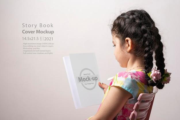 Bambina che legge un libro romanzo con copertina vuota nella parte anteriore del corpo