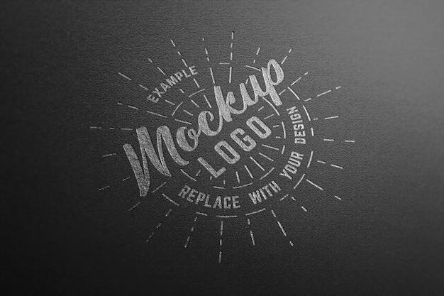 Mockup di logo su carta nera con effetto argento