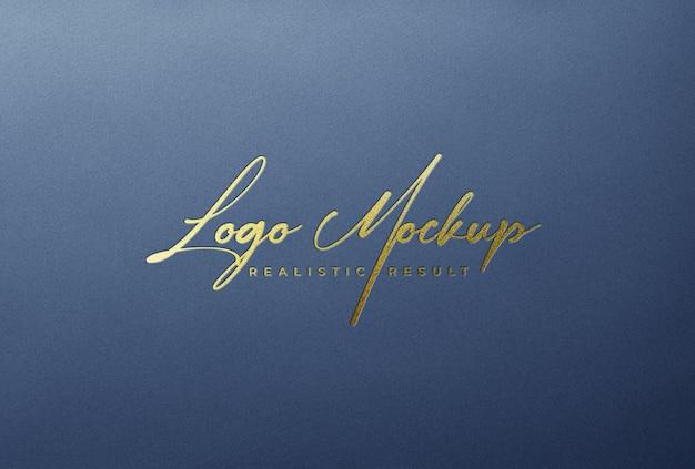 Logo mockup logo stampato in lamina d'oro su carta grigio blu