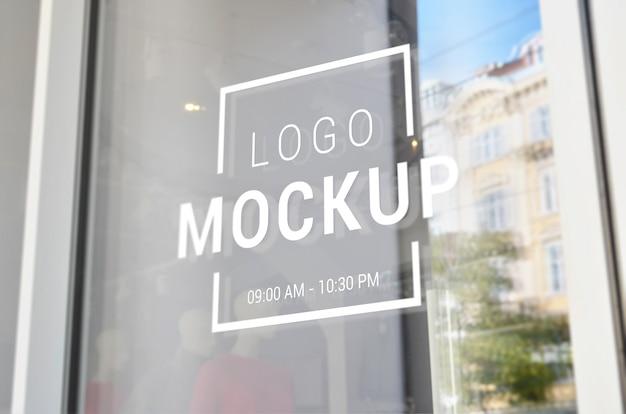 Logo mockup sulla vetrina della porta d'ingresso del negozio