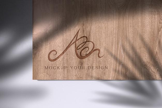 Logo su mockup di legno con foglia ombra Psd Premium
