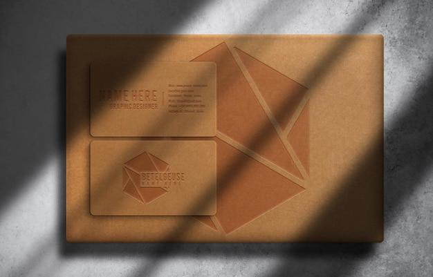 Scatola di lusso in carta marrone goffrata e biglietto da visita vista dall'alto mockup