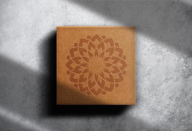 Mockup di scatola quadrata marrone con logo in rilievo di lusso