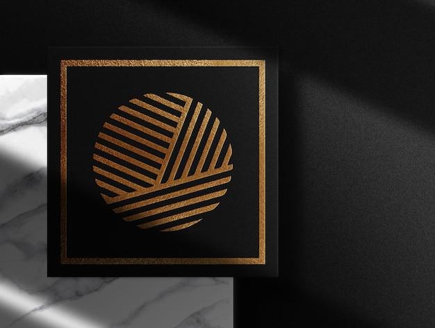 Vista dall'alto di carta nera goffrata in oro di lusso con mockup di podio in marmo