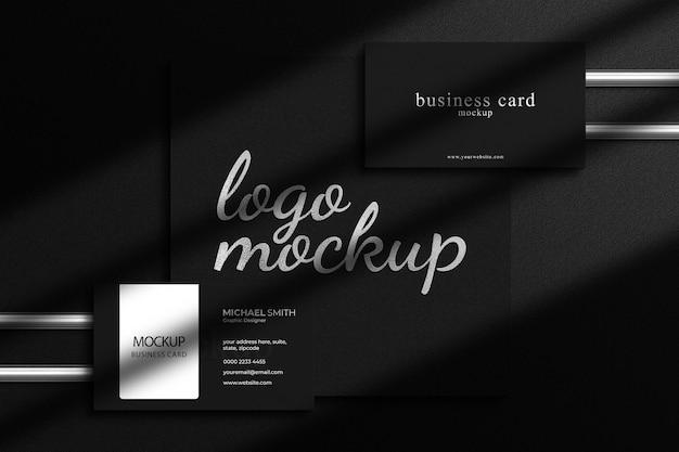 Modello di logo di lusso in lamina d'argento con mockup di biglietti da visita di lusso e sovrapposizione di ombre