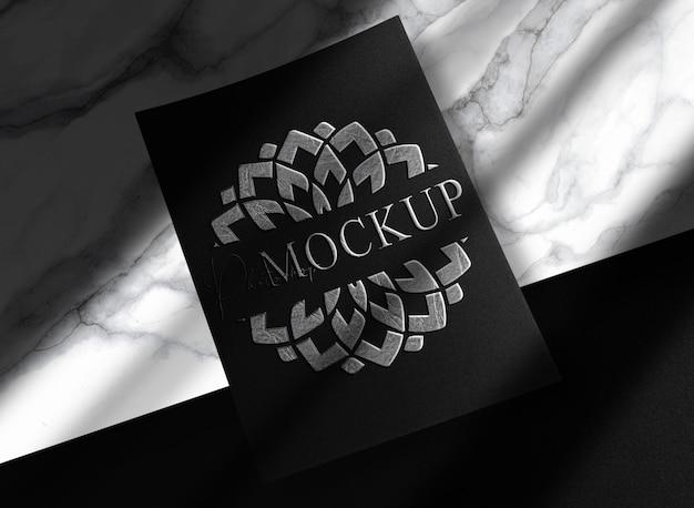 Mockup di carta goffrata in argento laminato di lusso con marmo modium
