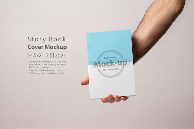 Mano maschio che tiene un catalogo di libri chiuso con mockup di copertina vuota Psd Premium