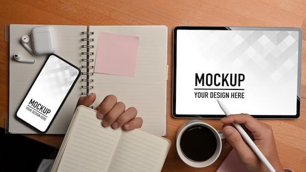 Mano maschio che tiene il libro di pianificazione e la tazza di caffè mentre si lavora con tablet e smartphone