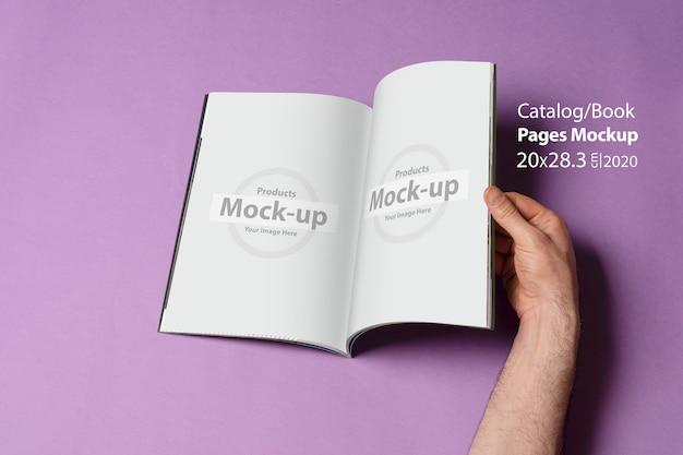 La mano maschio ha aperto un libro-catalogo isolato