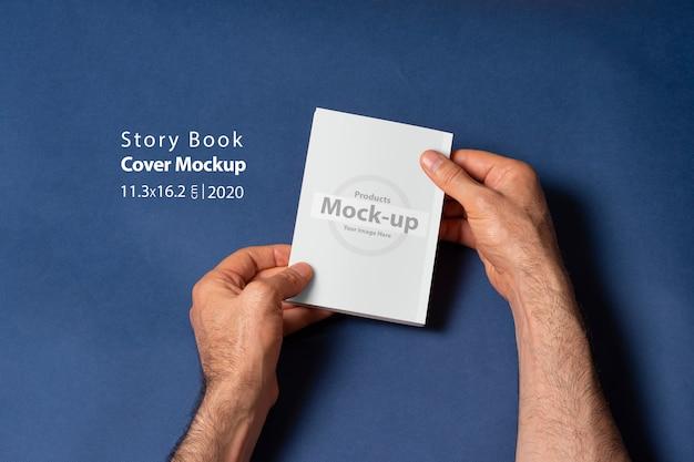 Mani maschili in possesso di un libro-catalogo a storia chiusa con copertina vuota