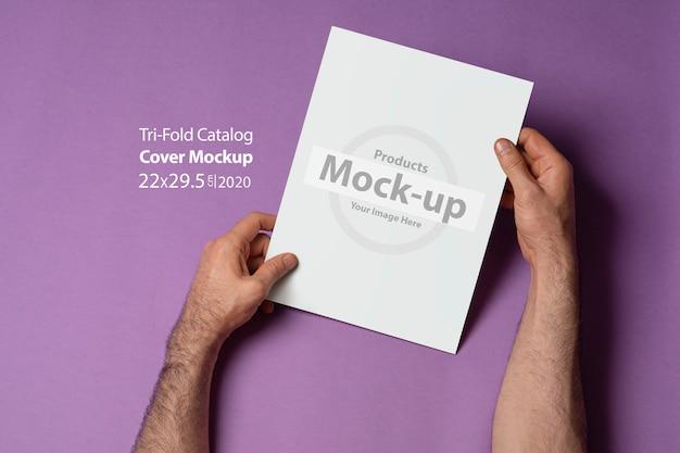 Mani maschii che tengono un catalogo ripiegabile chiuso con copertina vuota sulla superficie viola