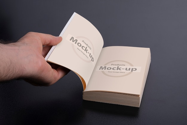 Una mano di uomo che apre un romanzo di serie mock-up