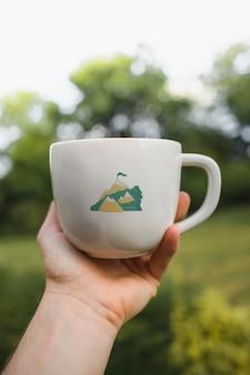 Uomo che tiene un modello di tazza di caffè bianco in un parco