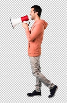 Uomo in una felpa rosa che urla attraverso un megafono per annunciare qualcosa in posizione laterale