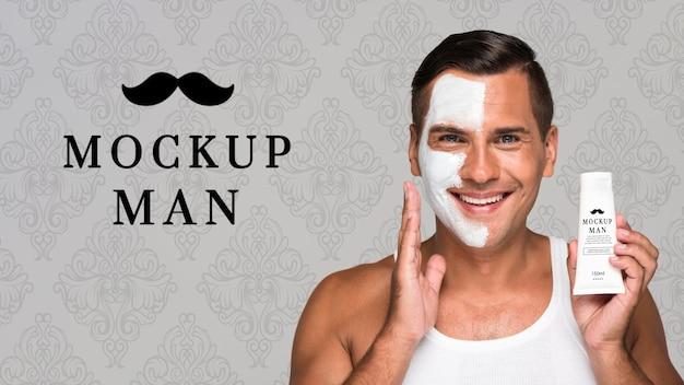 Uomo che utilizza la crema per il viso mock-up vista frontale